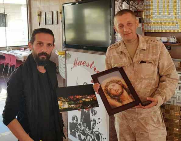 NDF commander in Suqaylabiyah, Nabel Abdulah, meets with a Russian army captain holding a picture of Jesus Christ.