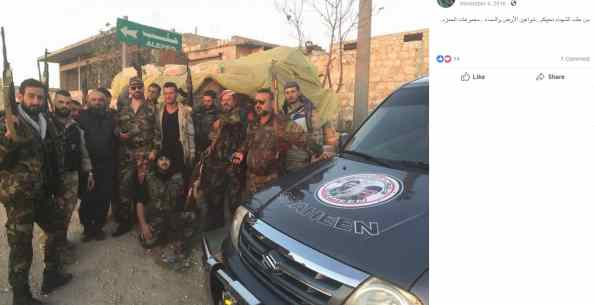 "Ahmed Shaheen (fifth from right, standing) and Yusuf Shaheen (right on Ahmed, hat and sunglasses) alongside ""Hamza Groups"" fighters and a truck with the Shaheen Groups emblem in Aleppo."