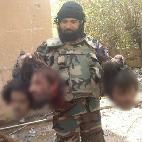 "A fighter in the Tiger Forces ""Cheetahs Groups"" posing with three severed heads, likely around Shaer, East Homs, in December 2014."
